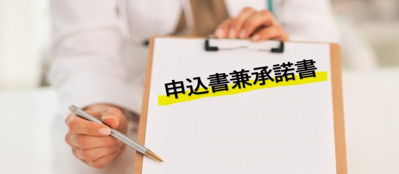 白衣を着た薬剤師がアンケート板の中にある文字、申込書兼承諾書をペンで示している
